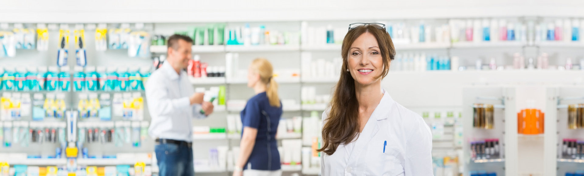 female pharmacist with customer buying at her back